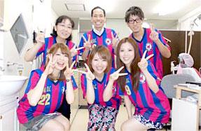サッカーチームのユニフォームを着た院長とスタッフ
