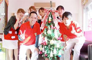 クリスマスツリーを囲む院長とスタッフ